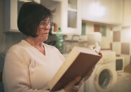Senior woman sitting in laundry room and reading book