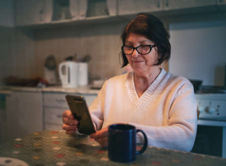 Smiling elderly woman sitting in kitchen and surfing on internet on mobile phone
