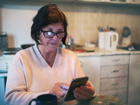 Elderly woman sitting in kitchen and surfing on internet on mobile phone