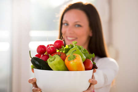 Close up of vegetables in bowl holding young pretty woman in kitchen
