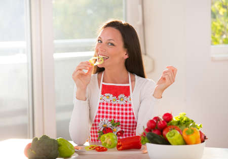 Happy young woman sitting at table with vegetables in bowls and eating slice of pepper