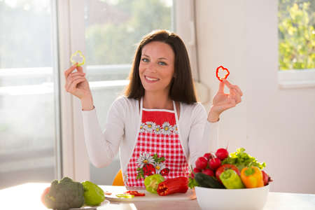 Happy young woman sitting at table with vegetables in bowl and holding pepper slices in hands