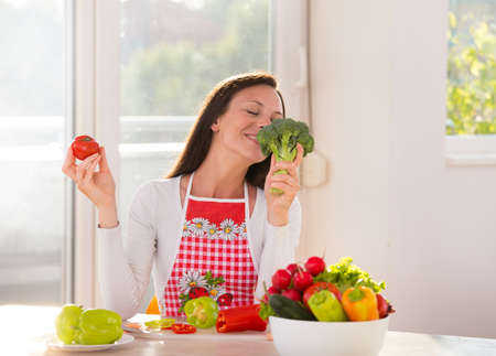 Satisfied woman sitting at kitchen table with vegetables in bowl and plates and enjoying smell of broccoli Archivio Fotografico