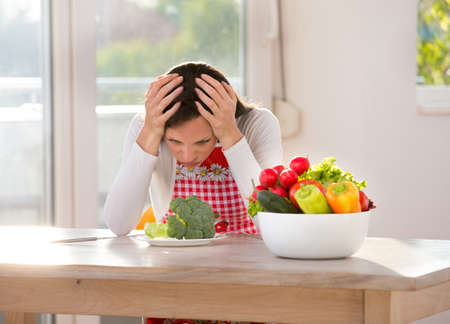 Pretty woman unhappy because of healthy food. Holding head with hands above broccoli in plate on kitchen table