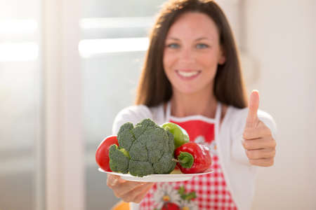 Pretty yoing girl holding plate with vegetables in one hand and showing thumb up with other hand Archivio Fotografico