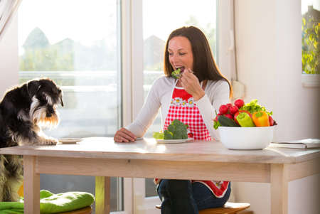 Girl and dog eating healthy food at kitchen table with vegetables in bowls Archivio Fotografico