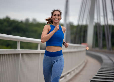 Fit young woman in sportswear jogging on bridge during day. Healthy and active lifestyle concept Archivio Fotografico