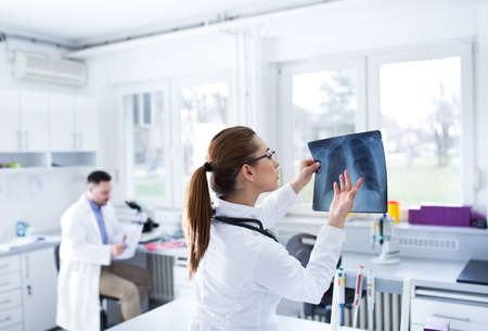 Two doctors working in laboratory reading x-ray lungs rib cage. Lab technicians diagnosing pulmonary medical illness.