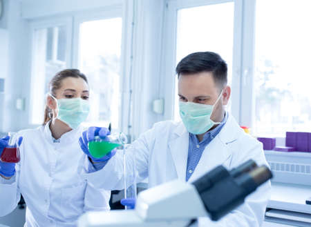 Young scientists researching experimenting holding erlenmeyer flask. Man and woman lab technician in laboratory measuring liquid wearing face mask.