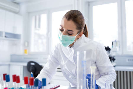 Lab technician working monitoring writing experimenting using vials. Young female scientist doing medical research wearing face mask in laboratory.