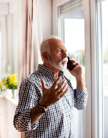 Senior standing next to window looking out speaking on the mobile phone upset hand raised Archivio Fotografico
