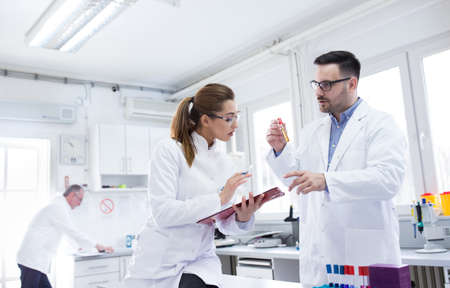 Two young lab technicians scientists talking experimenting in laboratory. Man and woman doctors holding vial clipboard doing research.