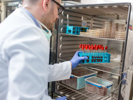 Man working in laboratory putting samples in vials into incubator. Yound scientist doctor experimenting wearing protective gloves lab coat face mask Archivio Fotografico