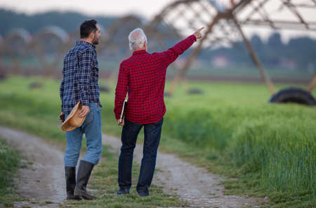 Two men walking next to field looking pointing showing center pivot irrigation system. Farmers surveying land modern agriculture.