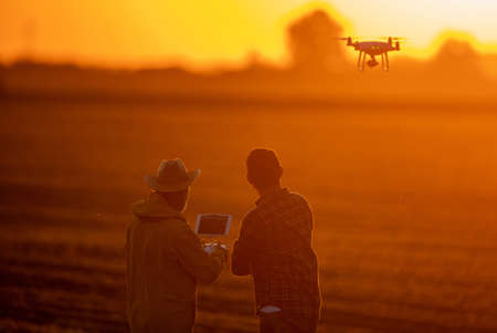 Two farmers standing in field using modern technology for agriculture flying drone at sundown