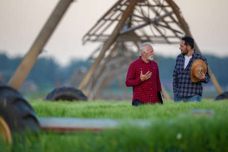 Two farmers standing in field talking showing center pivot irrigation system. Two men speaking explaining agriculture innovation.