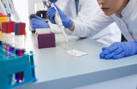 Young scientist using modern medical equipment in laboratory. Woman with pipette preparing samples for microscope.