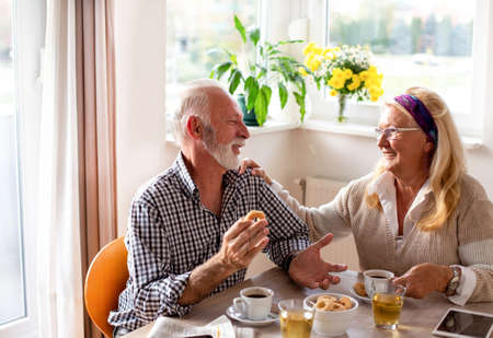 Senior couple speaking over coffee biscuits smiling touching shoulder. Man and woman in dining room relaxing. Archivio Fotografico