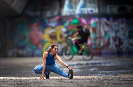 Sporty girl stretching legs before exercise. Workout in urban ambient