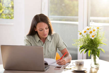 Young student sitting at table learning writing taking notes. Woman working from home using laptop modern technology
