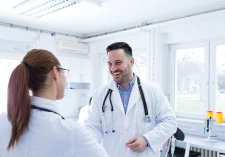 Man and woman in hospital laboratory lab greeting. Two young doctors clinicians smiling at clinic. Archivio Fotografico