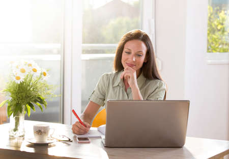 Young student sitting at table studying learning reading taking notes. Woman working from home remotely using laptop.