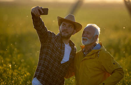 Two farmers standing in field taking selfie using phone smiling happy. Men marking in agribusiness with photo outdoors at sundown. Archivio Fotografico