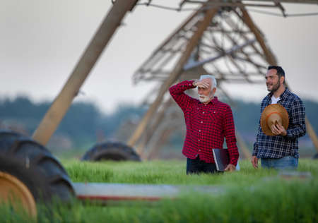 Farmers standing in field looking surveying. Two men next to center pivot irrigation system modern agriculture. Archivio Fotografico
