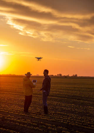 Happy farmers using drone and modern technology to survey land at sunset