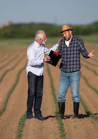 Two men talking in corn field persuading. Businessman holding clipboard showing explaining to worried farmer.