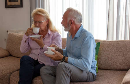 Two seniors on couch sofa speaking drinking tea coffee. Man holding cup and saucer and woman drinking.