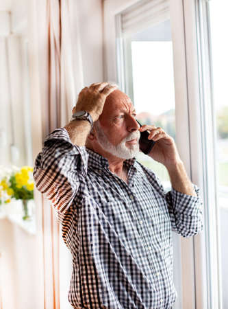 Senior man standing in front of window looking out talking on the phone worried upset with hand on head.