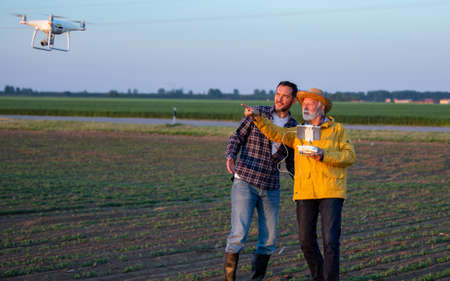 Men using modern technology to survey land standing in field using drone Archivio Fotografico