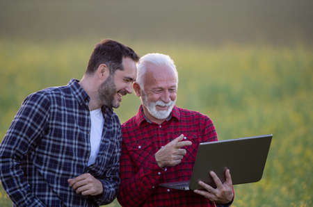 Farmers using laptop outside for agriculture.. Two men standing in field  pointing showing smiling at screen.