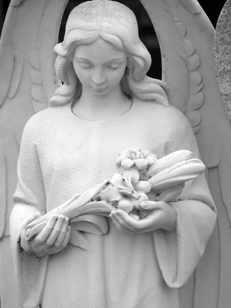 a white stone angel with flower