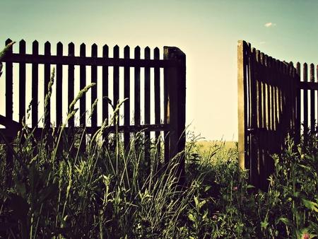 An old wooden fence with an open gate door  Reklamní fotografie