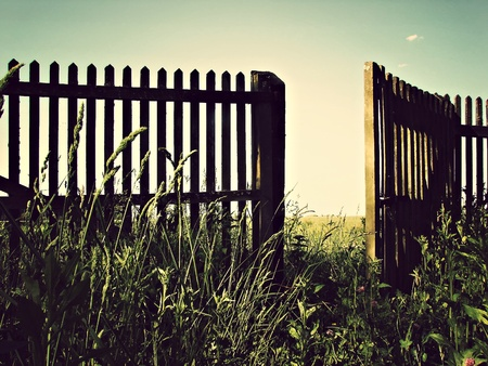 An old wooden fence with an open gate door  Banque d'images