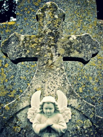 a stone cross with an angel on it  photo