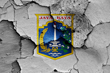 disintegrate: flag of Jakarta painted on cracked wall Stock Photo