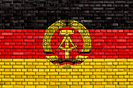 east of germany: flag of East Germany painted on brick wall