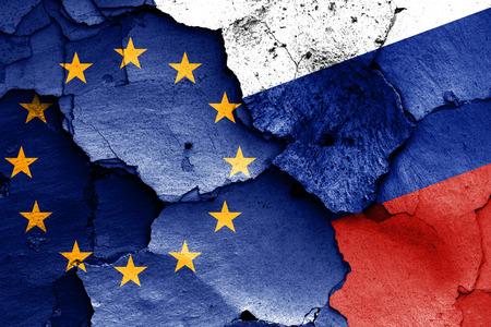 ひびの入った壁に欧州連合とロシアの国旗が描かれました。 写真素材