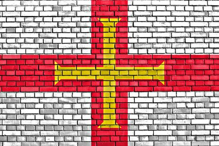 bailiwick: flag of Guernsey painted on brick wall