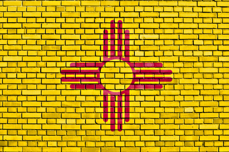 flag of New Mexico painted on brick wall