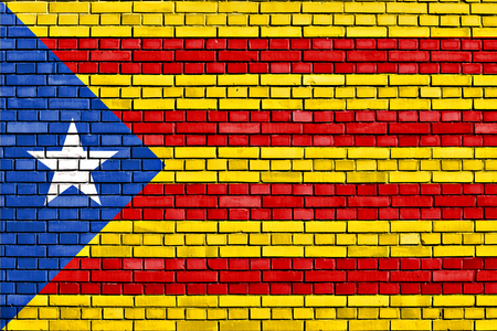 separatist: flag of Catalan independence movement painted on brick wall