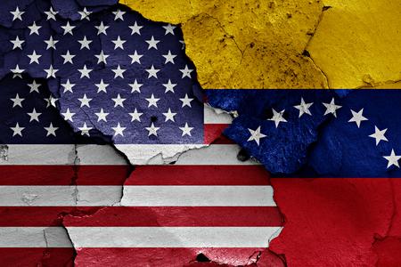 ひびの入った壁に米国およびベネズエラの国旗が描かれました。 写真素材