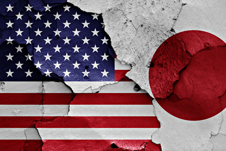 international crisis: flags of USA and Japan painted on cracked wall