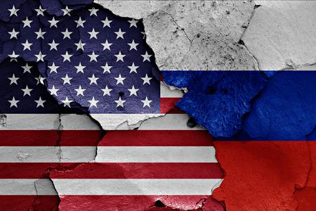 ひびの入った壁に描かれたアメリカとロシアの国旗