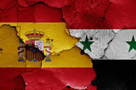 flags of Spain and Syria painted on cracked wall Stock Photo