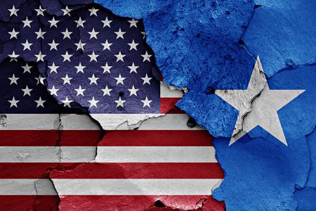 vlaggen van de VS en Somalië geschilderd op gebarsten muur Stockfoto