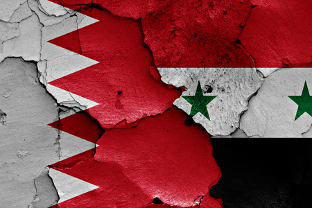 international crisis: flags of Bahrain and Syria painted on cracked wall